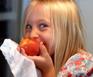 A young child eating a Georgia peach and enjoying every bite