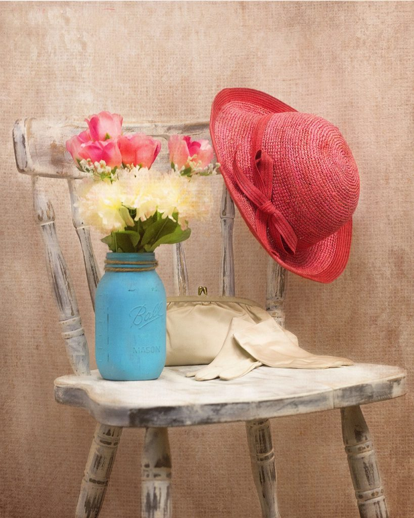 A restored chair with a vase of flowers, nag, gloves and hat placed on it