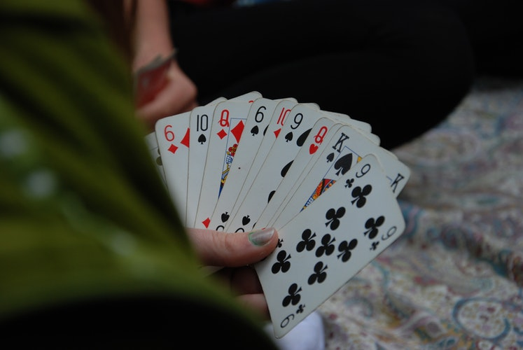 A person's hand during a card game.