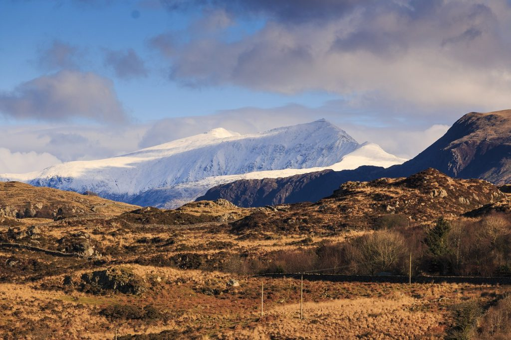 A panoramic view of Snowdon covered in snow in the heart of North Wales.