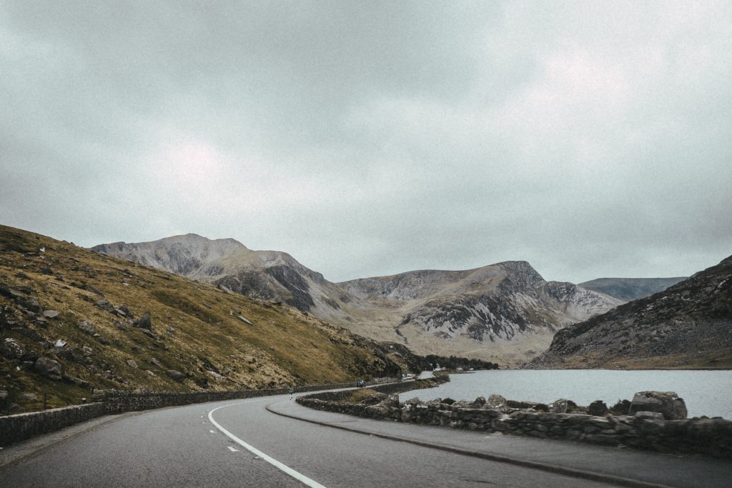 A tarmac road winding through mountains in Wales.