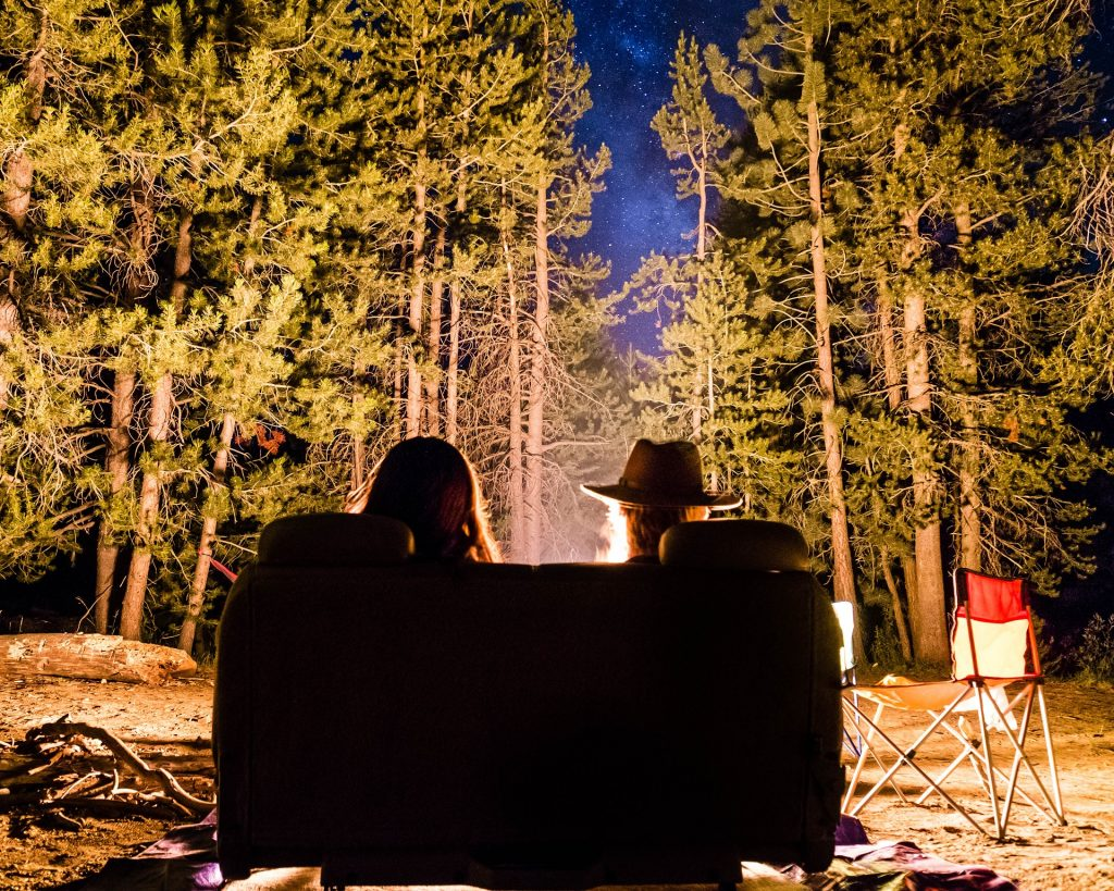 Couple sat on sofa, outside, in front of campfire.f